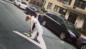 Couple wed on sidewalk as friend officiates from apartment window