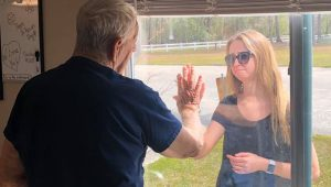 Woman shares engagement news through care facility window