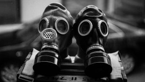Couple pose with gas masks and 'dead' guests for wedding photos